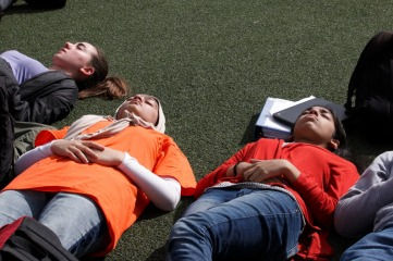 Students lay in the sun on the football field during the 17 minutes of silence. The crowd took the silence seriously, appreciating the moment of memorialization. (Alexandrianna De La Cerda)
